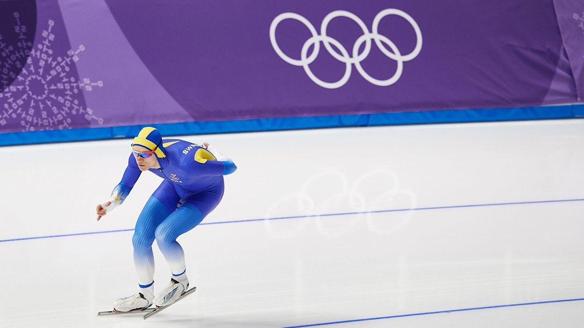 På fotot ser man en skridskoåkare i svensk dräkt. Bakom honom syns symbolen för OS med fem runda ringar.
