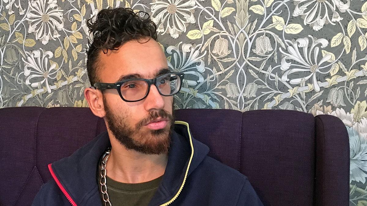 Barsam har glasögon och en tjock kedja runt halsen. Han har en huvtröja på sig. Frisyren är kortklippt, men med en lång och lockig lugg. Barsam har skägg.