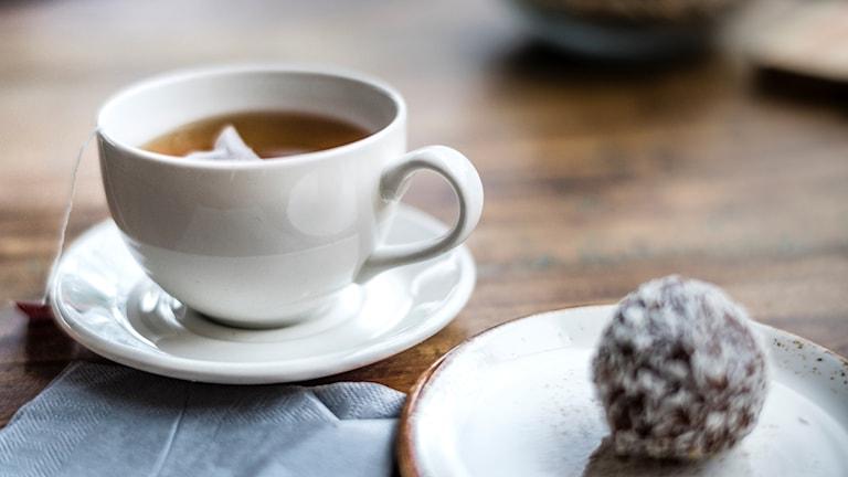 Fotot visar en kopp te och en chokladboll
