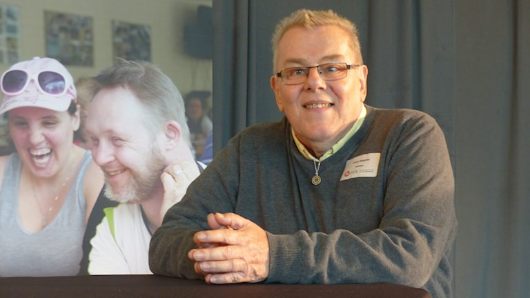 Conny Bergqvist står vid ett bord och ler in i kameran. Han har glasögon och kort hår.