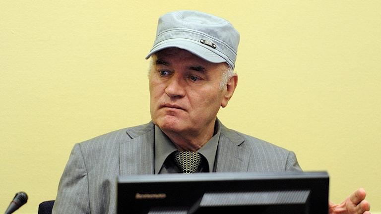 Fotot visar militären Ratko Mladić i en keps och en grå kostym.