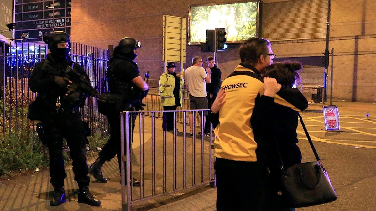En ung tjej med handväska blir tröstad av en kille. Hon gråter mot hans axel. Bredvid står poliser.