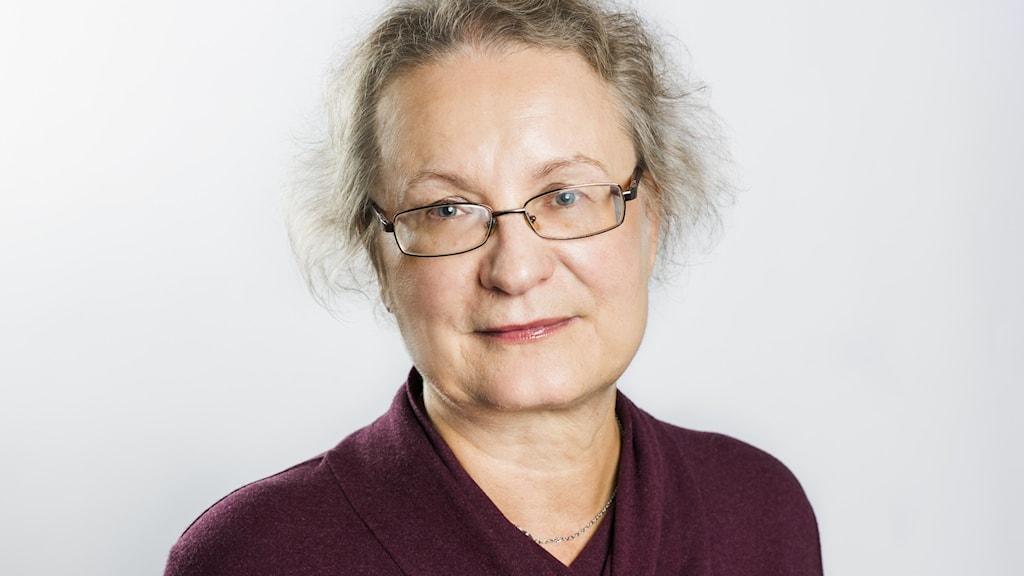 På bilden ser man en kvinna med glasögon och som har en lila blus på sig.