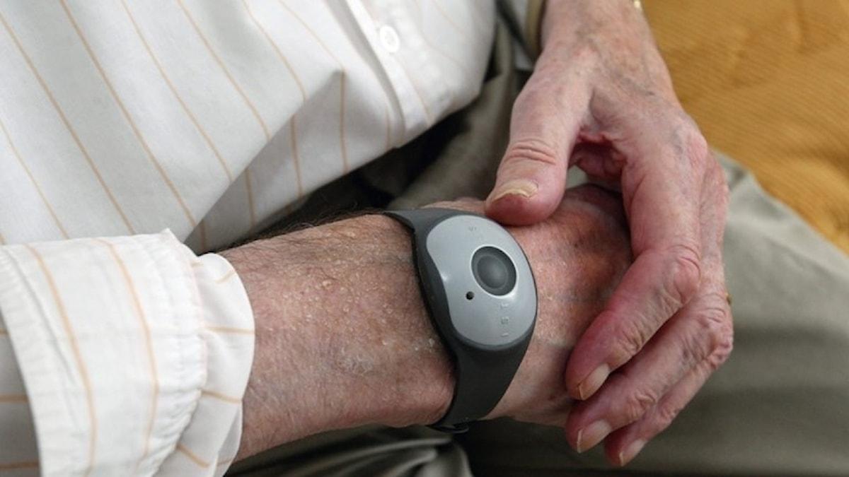 Fotot visar en äldre persons händer där ett trygghetslarm sitter kring den ena handleden.