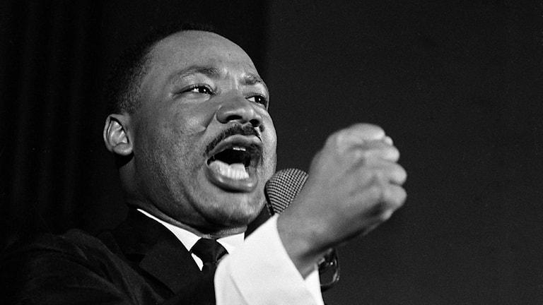 På fotot ser man Martin Luther King. Han har mörk hudfärg och är klädd i kostym, vit skjorta och slips.