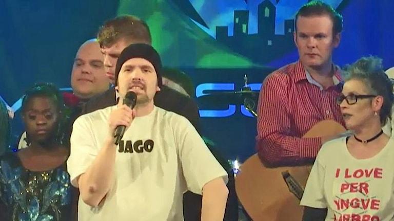"""På foto har Kenneth en svart mössa och en vit T-shirt med texten """"Jago""""."""