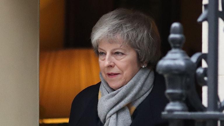 På fotot syns Theresa May. Hon har grått hår och en grå halsduk runt halsen.