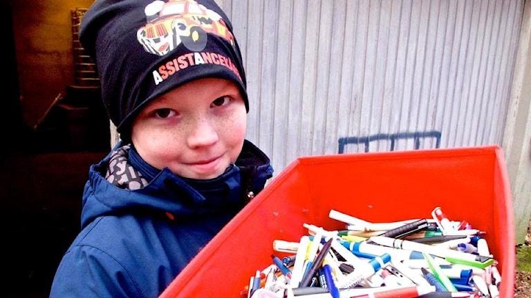Adam Karlsson med en låda full med pennor.