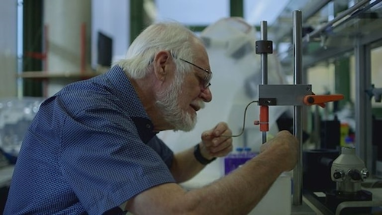 Fotot visar en man i blå skjorta och vitt hår som håller på i ett laboratorium.