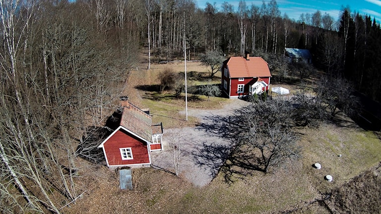 Två röda hus med träd omkring. Här mördades två personer.