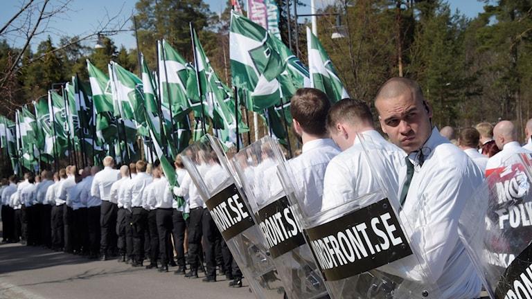På fotot har nazisterna vita sjortor, gröna flaggor och sköldar av genomskinlig plast.