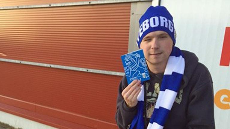 På fotot har Jakob mössa och halsduk i fotbollslagets färger och han håller upp sitt årskort.