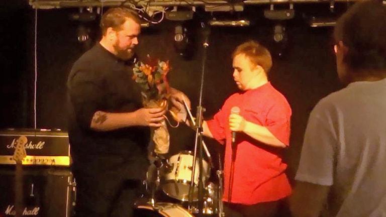 På fotot får Mattias ta emot blommor. Han håller en mikrofon i handen.