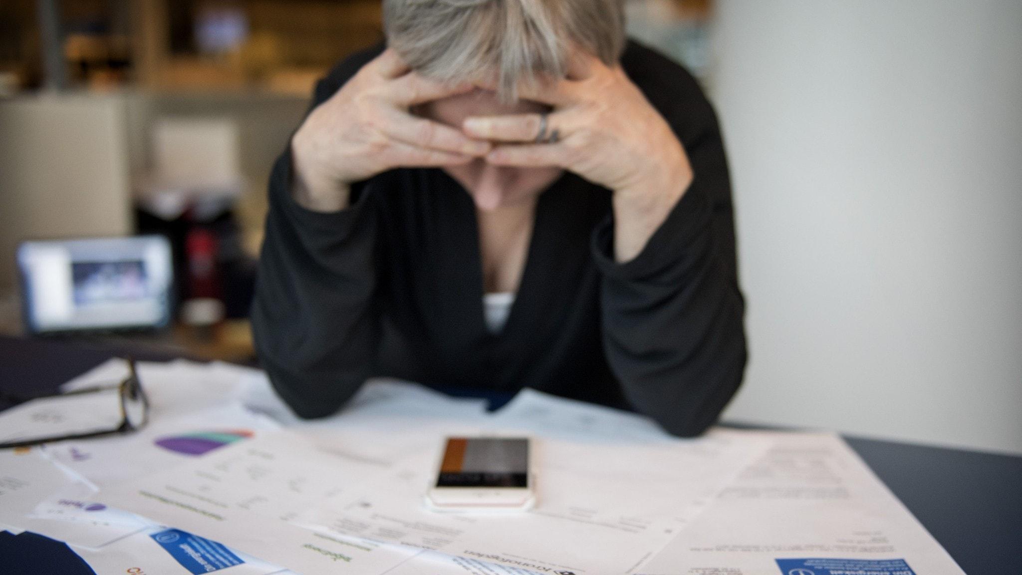 Kvinna sitter framför bord med räkningar. Håller huvudet i händerna.