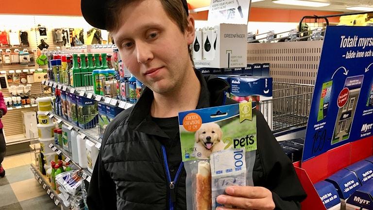 På fotot ser man Rickard. Han är klädd i keps och täckjacka. Han håller fram en påse med hundgodis och en hundralapp.