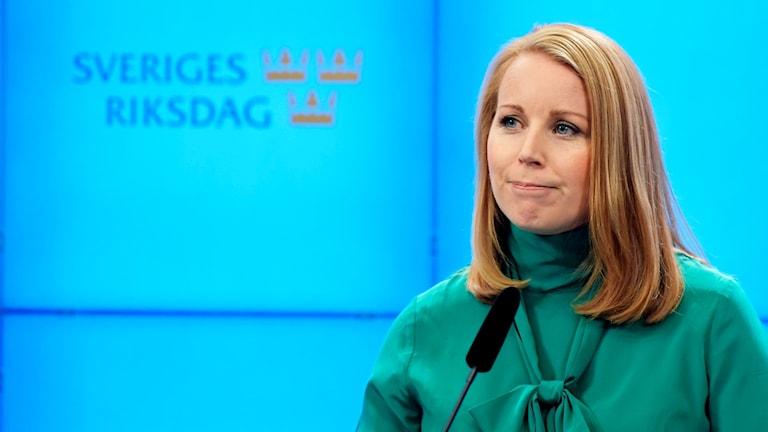 På fotot syns Annie Lööf. Hon har gröna kläder på sig.