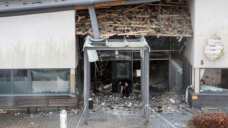 På fotot har glasväggen sprängts bort och taket är trasigt. På väggen finns resterna av en skylt med polisens symbol på.