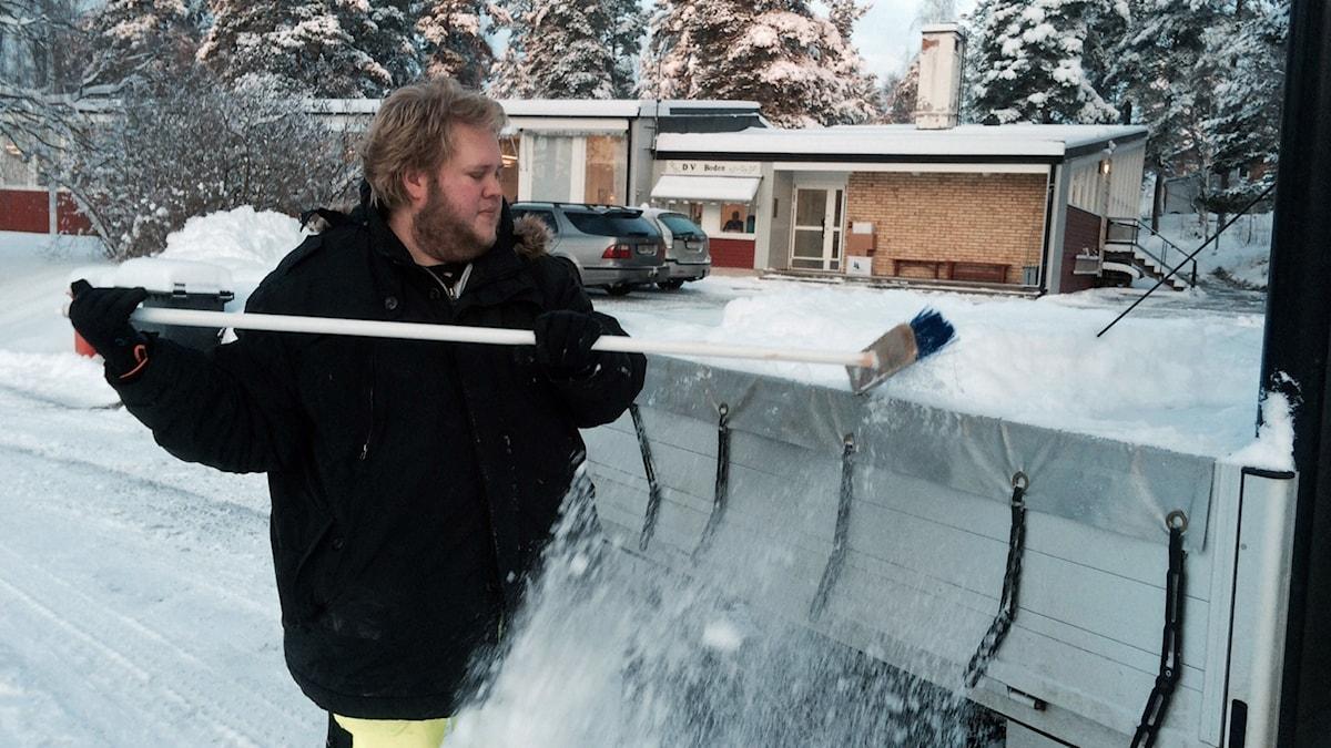 Med en sopkvast föser han bort snön.