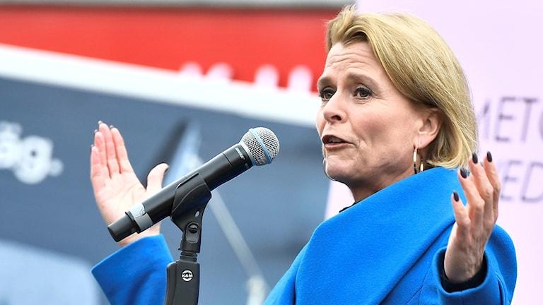 På fotot står Åsa Regnér och håller ett tal. Hon har en kappa i en stark blå färg.