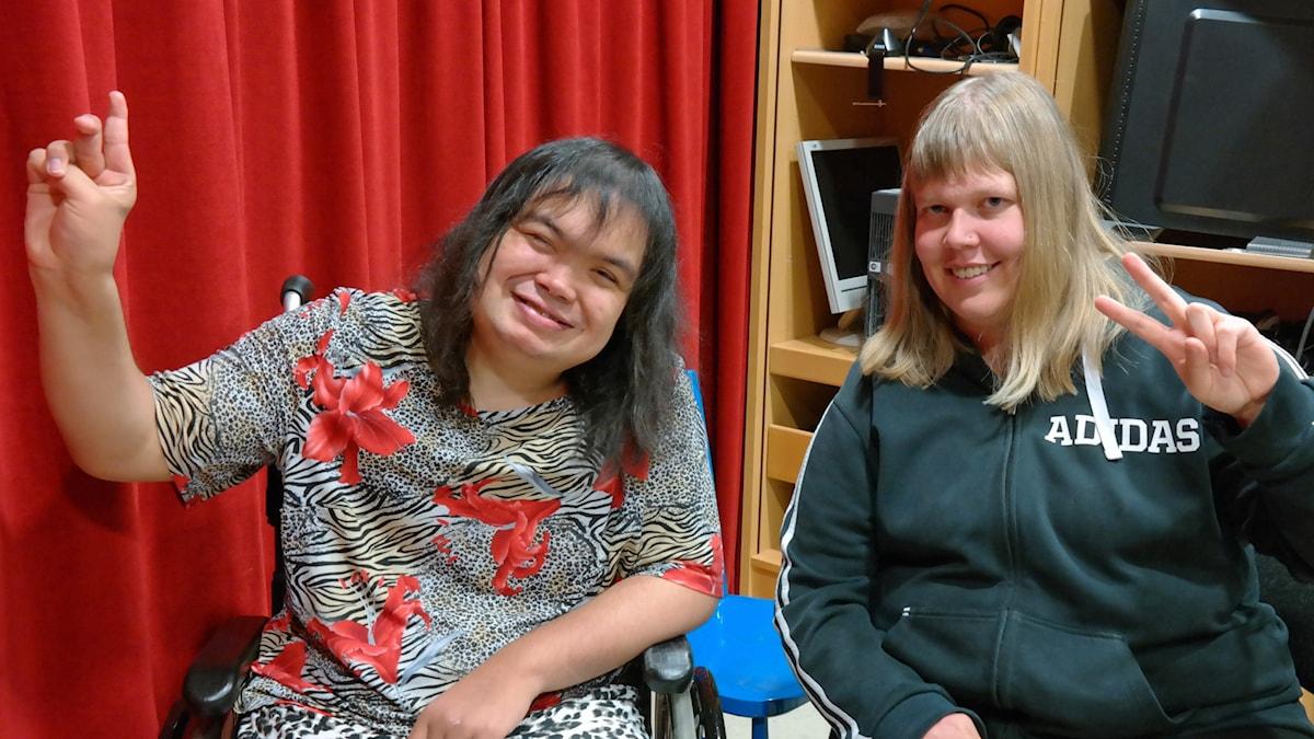 Emma och Matilda gör V-tecken med fingrarna. Emma sitter i rullstol.