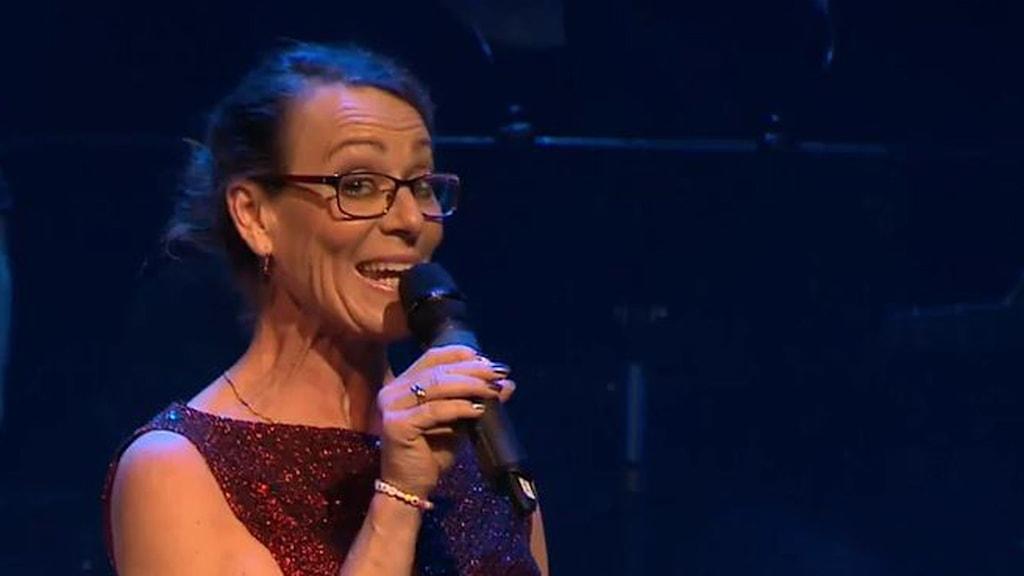 På fotot pratar Ann Epstein i en mikrofon. Hon är klädd i en festklänning och har glasögon.