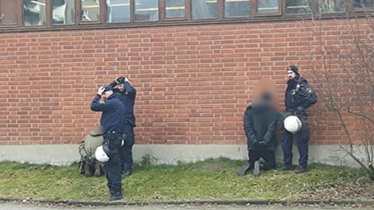 De misstänkta står på knä med ansiktet mot skolans vägg.