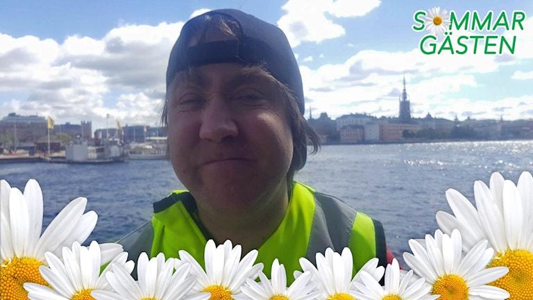 Anders står nere vid Mälarens strand. På andra sidan vattnet syns Stockholms stadshus.