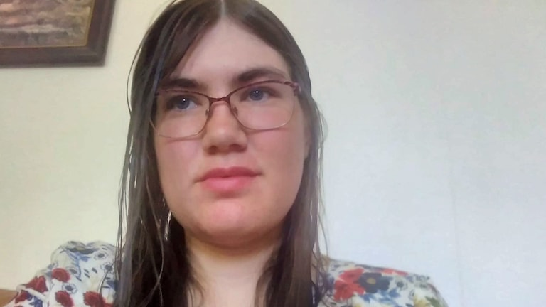 På fotot ser man Camilla. Hon har glasögon och långt mörkt hår.