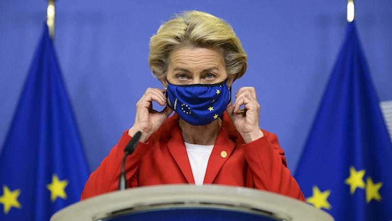 På bilden ses EU-kommisionens ledare Ursula von der Leyen. Hon har på sig ett munskydd som ser ut som EU:s flagga, blå med gula stjärnor.