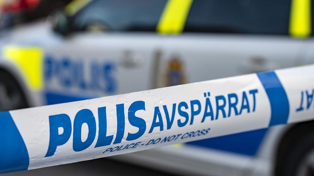 """På bilden ser man orden """"Polis Avspärrat"""" på en plastremsa, och en polisbil bakom."""