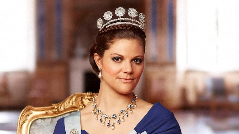 På fotot ärkronprinsessan klädd i en blå klänning och hon har en tiara i håret och ett stort halsband om halsen.
