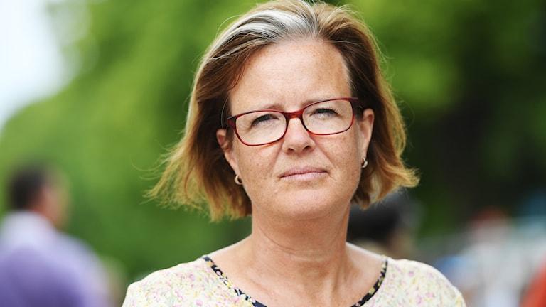 En kvinna i brunt pageklippt hår med glasögon