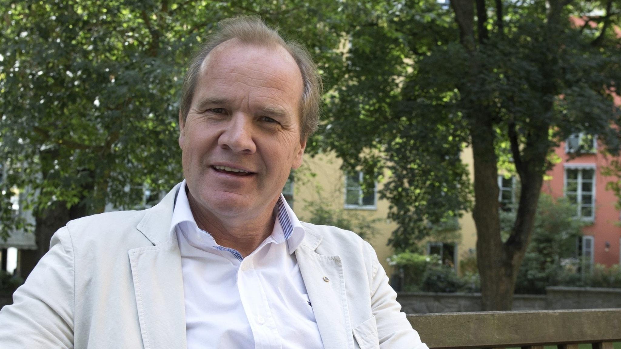 På fotot sitter Anders Lago på en parkbänk. Han är klädd i en ljus kavaj och vit skjorta.