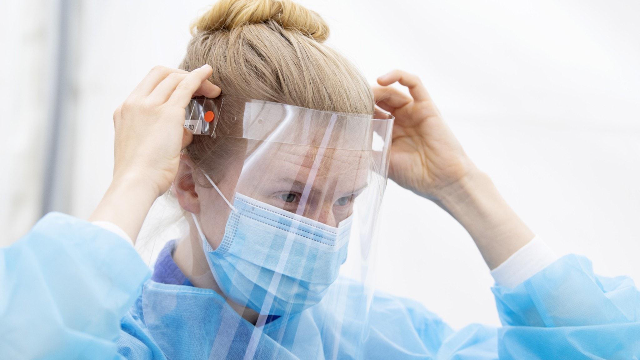 På fotot syns en kvinna med skyddsvisir för ansiktet.