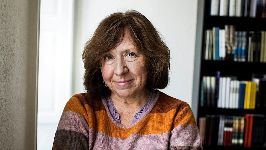På fotot har hon en randig tröja och står framför en stor bokhylla.
