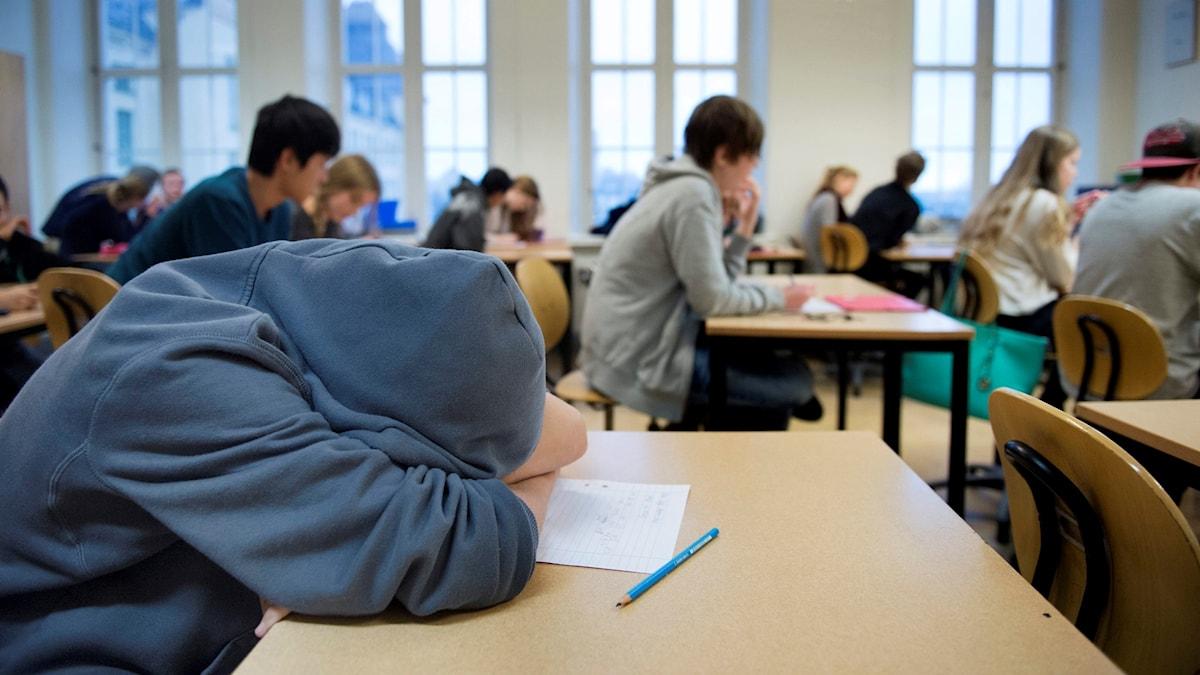 På det här fotot syns ett klassrum. En av eleverna har huvtröja på sig och har lagt ner huvudet mot bänken.
