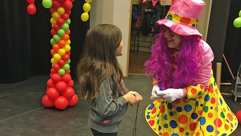 På fotot pratar en clown med en flicka. I rummet finns många ballonger.