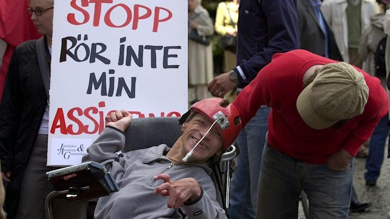 Fotot visar en kille i rullstol och hans personaliga assistent.