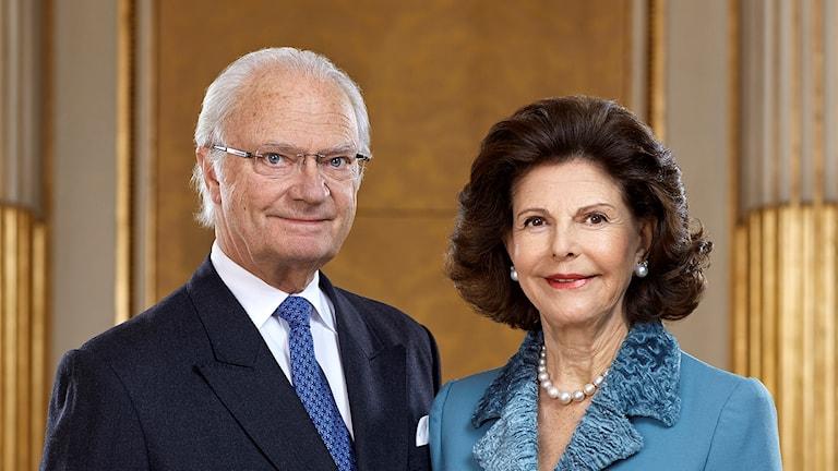 På fotot ser man kungen och drottningen. Han är klädd i kostym och har en blå slips och hon har en blå dräkt och pärlhalsband.
