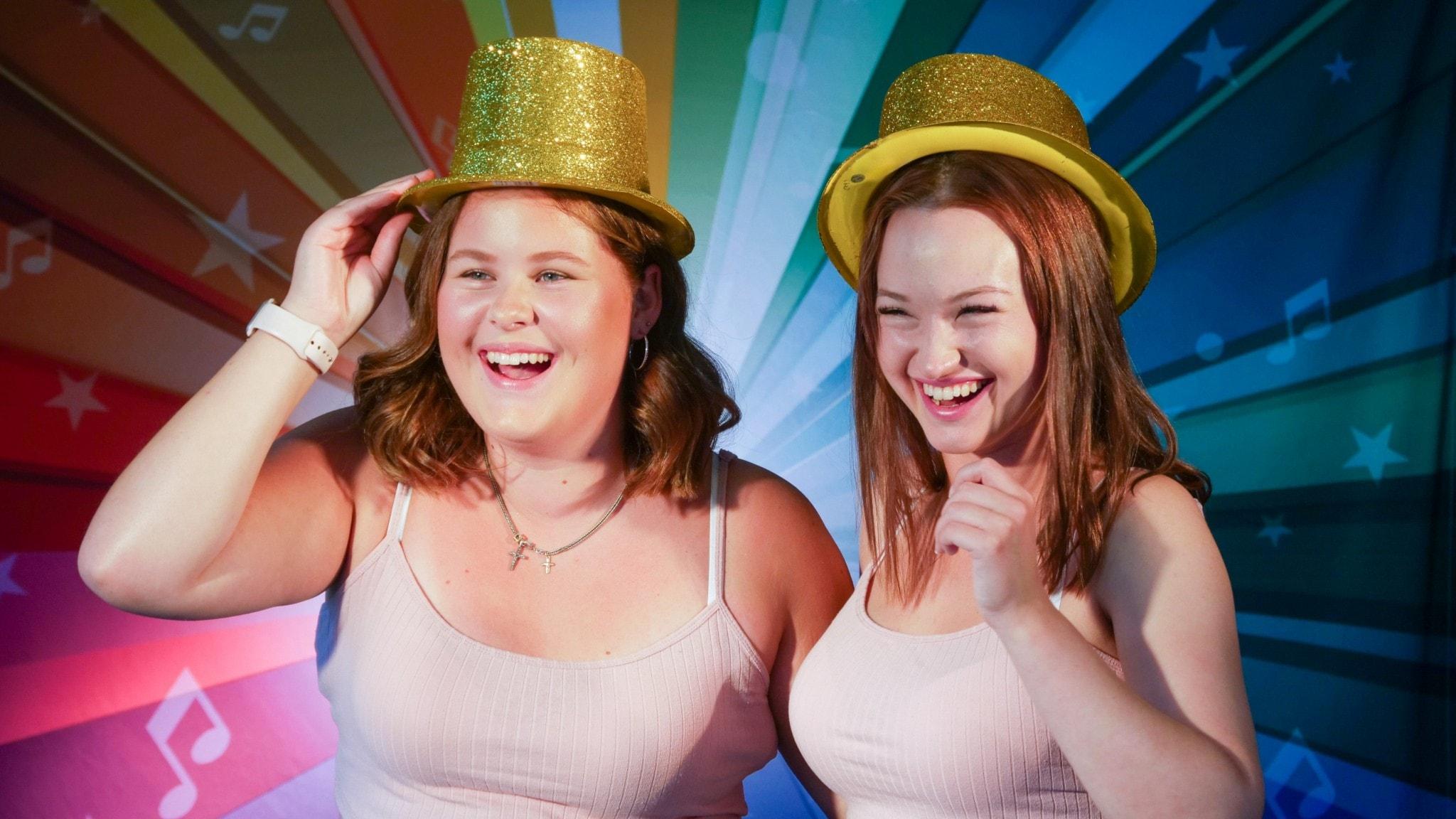 Anna Leander och Cilla Wickström har på sig guldfärgade hattar och ser glada ut.