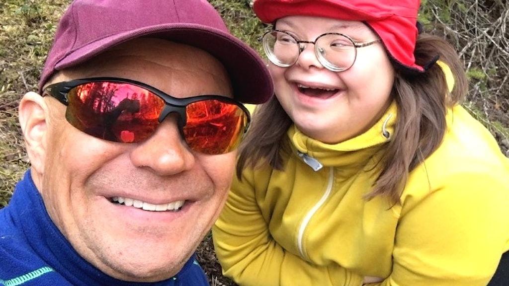 Per-Erik Kuoljok är same och tittar med ett leende in i kameran. Han bär en vinröd keps och solglasögon. Till höger är dottern maja, 18 år. Hon har downs syndrom, bär glasögon, och har en röd keps på huvudet, hon bär en gul jacka.
