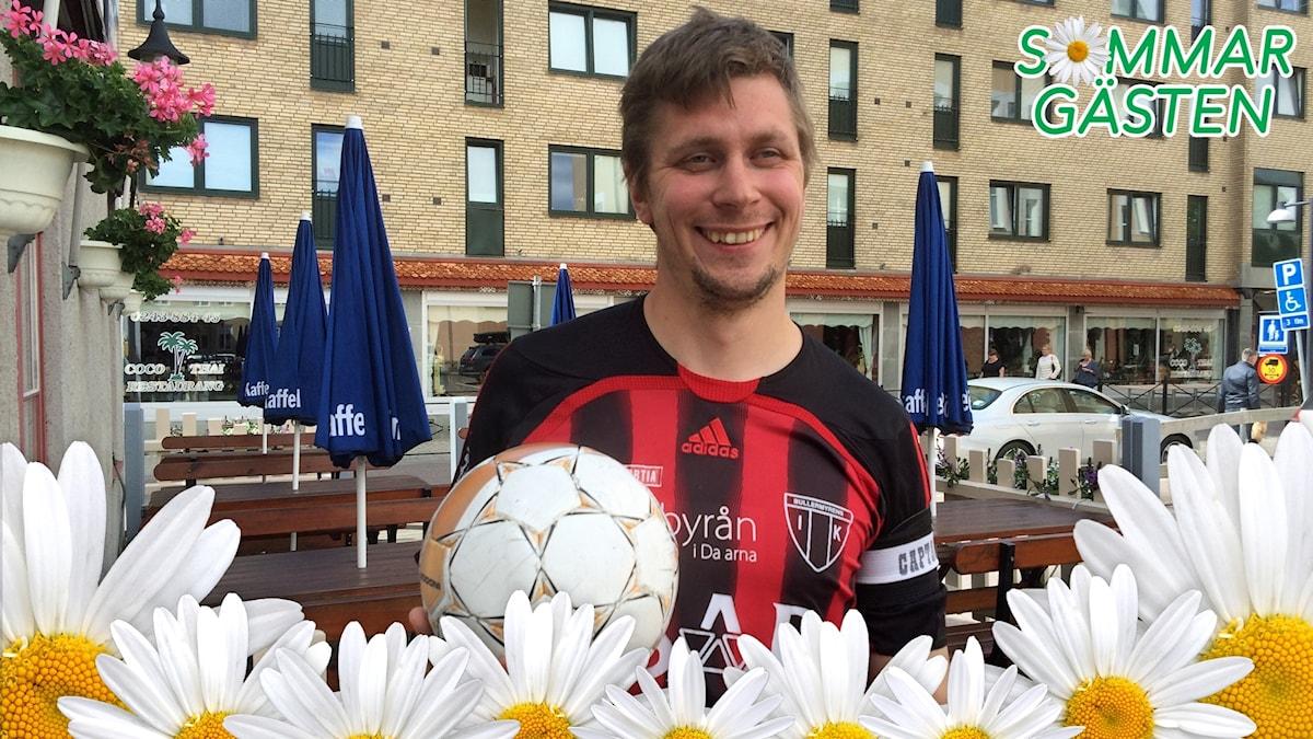 Tobias har fotbollskläder som är röda och svarta. Han håller i en fotboll.
