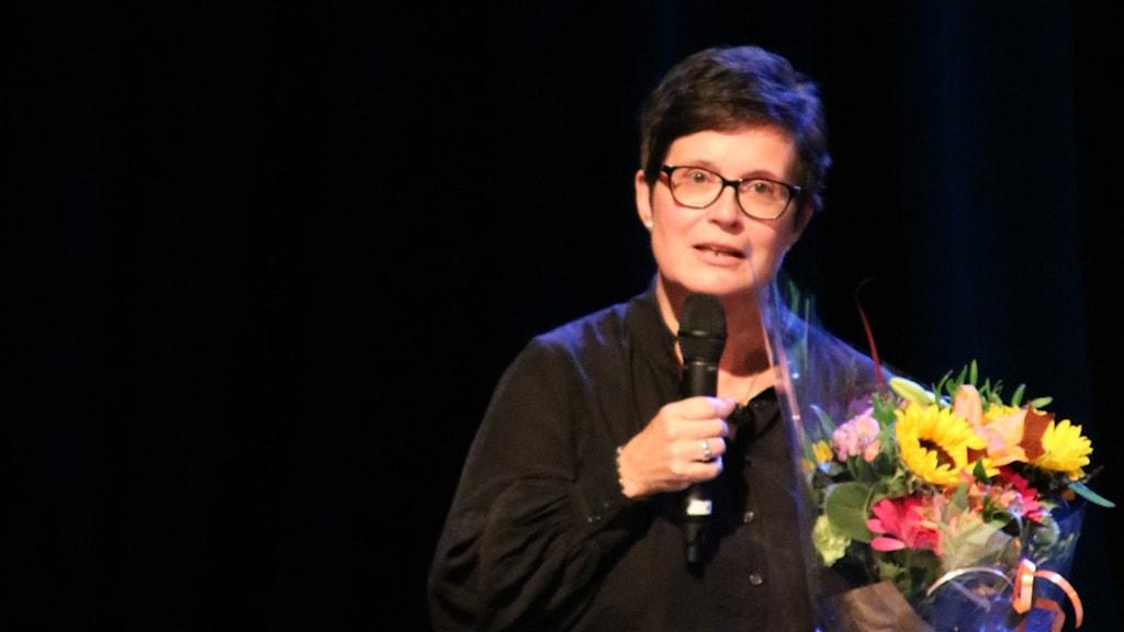 På fotot är Åsa Storck klädd i svart och rummet bakom henne är mörkt. Hon har fått blommor i många olika färger. Hon är kortklippt och har glasögon.