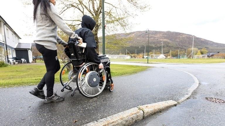 På bilden ser man en kvinna som skjuter en person i rullstol framför sig.