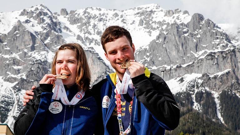 En tjej och en kille biter i varsin guldmedalj. Bakom dem syns höga bergstoppar.