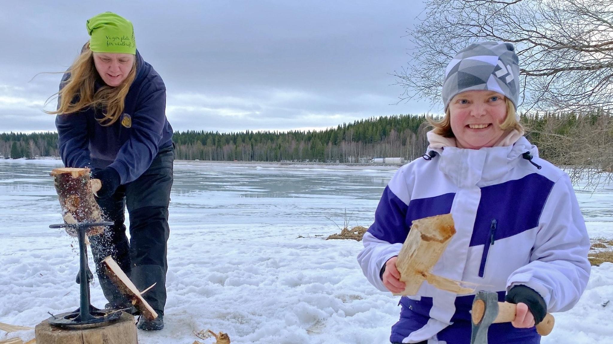 Två unga kvinnor som hugger vet ute i naturen på vintern.