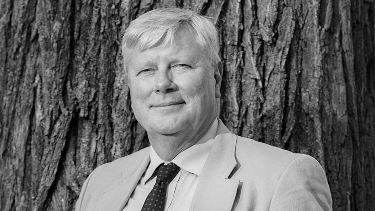 På fotot står Lars Ohly vid ett träd. Han är klädd i kostym, skjorta och slips. Fotot är svartvitt.
