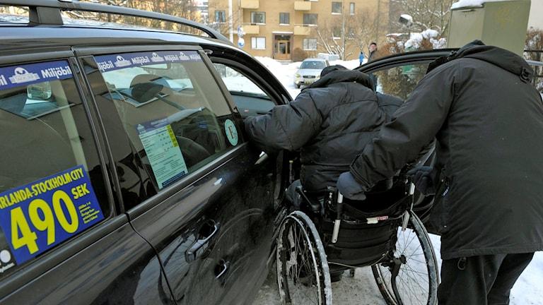 En person i rullstol får hjälp in i en taxibil.