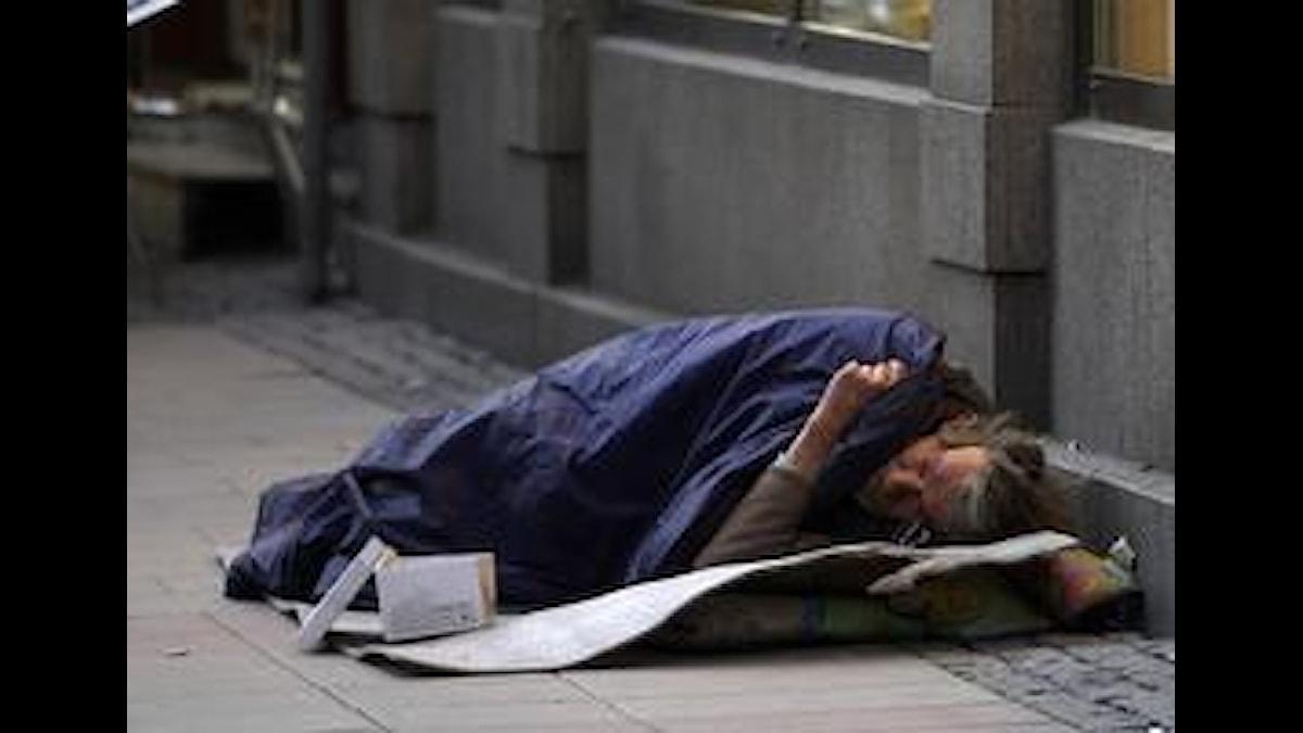 På bilden syns en man som är hemlös och som måste sova på gatan.