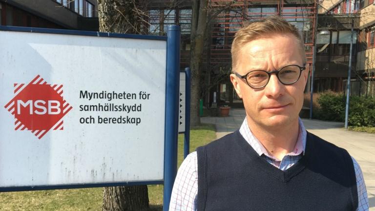 Fotot visar en vit skylt som det står MSB på och en man i glasögon och blå pullover.